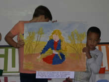 Children holding a picture of Ruth among the corn