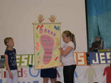 Child holding a banner of a footprint with two girls looking on