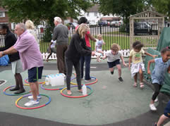 Adults standing in coloured rings on a playground while children run around them