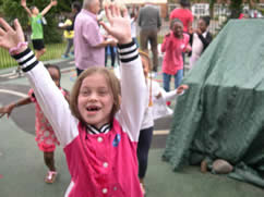 Happy girl holding her hands up in a playground among other children and adults