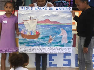 Children with a banner of a lake with a boat and Jesus standing on the water and lifting a sinking disciple