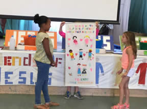 Girl hidden behind a banner with human figures holds it up while two other girls look on