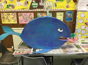 Cardboard model of a blue coloured whale blowing a spout from its blowhole