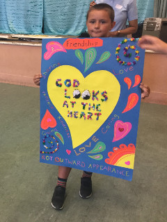 A boy holds a poster of a yellow heart with the words 'God looks at the heart'