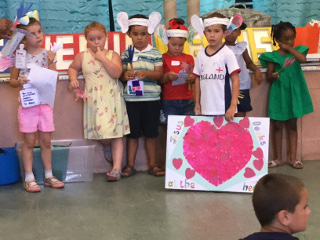Some children wearing paper ears, one holding a poster with a heart saying 'Jesus looks at the heart'