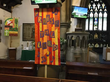 Banner of irregular vertical stripes of orange and gold and letters on dark squares spelling 'Praised the Lord'