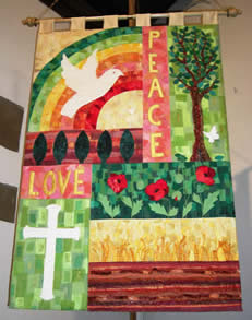 Top half has 'PEACE' vertically in yellow on rose, separating on the left a white dove flying in front of a red, yellow and green rainbow and on the right a dove flying to a green tree. Lower half has on the left the word 'LOVE' in yellow on rose over a white cross on variegated light green squares, and on the right a horizontal panel with three vivid poppies with leaves on a green leafy background above a row of yellow wheat above brown earth.