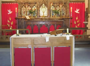 Altar with bright red curtains each side, each with a white dove flying towards the centre